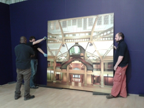 Technicians measuring a large painting