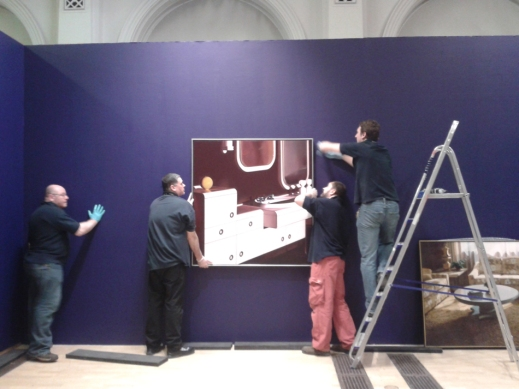 Technicians hanging a painting on the wall